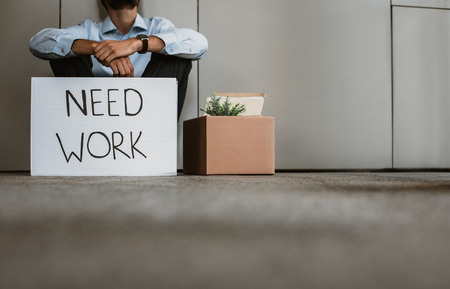 Low angle of laid off office worker sitting near box with belongings on floor indoor. He is putting placard showing his need for new job Stock Photo