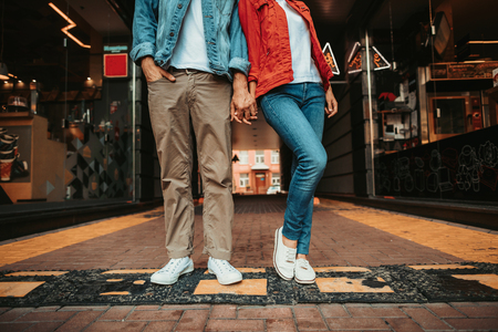 Male holding arm of young woman while locating outdoor near shop-windows. They having fun together while wearing white trainers and standing on road hump