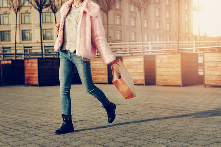 I am heading home. Cropped portrait of young lady in pink fur coat holding paper bag on sunny street