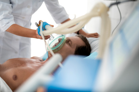 Close up portrait of middle aged man with oxygen mask lying in bed. Doctor hands using respiratory equipment to restore lungs function of gentleman Stockfoto