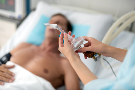 Mechanical ventilation. Close up of female hands preparing tube of breathing machine while middle aged man lying in hospital bed