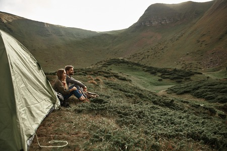 Good day. Peaceful young couple sitting next to their tent while being in the mountains and enjoying the view