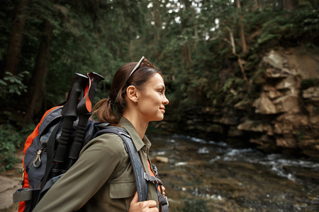 Active girl. Positive confident young woman smiling and enjoying her hiking trip while carrying heavy backpack with walking sticks