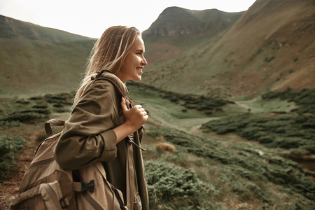 Carrying everything. Cheerful emotional young woman holding her big backpack and enjoying the view in the mountains