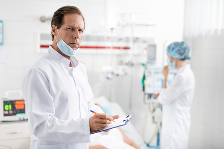 Waist up portrait of handsome surgeon with protective mask on chin noting information about patient while looking at camera with serious expression. Nurse near breathing machine on blurred background