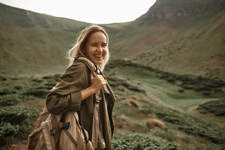 Laughing. Cheerful expressive young woman feeling delighted and laughing while being in the mountains with her big backpack