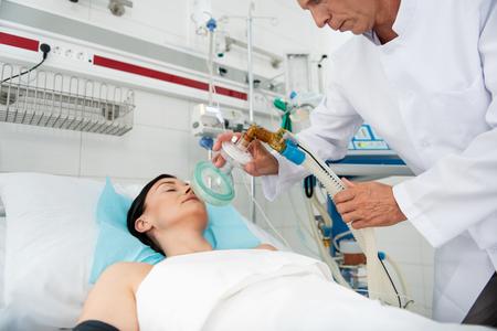Paciente de sexo femenino acostado en la cama de hospital y recibiendo ventilación mecánica. Terapeuta recortada en bata de laboratorio blanca con equipo respiratorio Foto de archivo