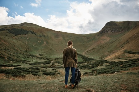 Looking at hills. Young woman wearing casual clothes and carrying her backpack while being in the mountains and enjoying the view