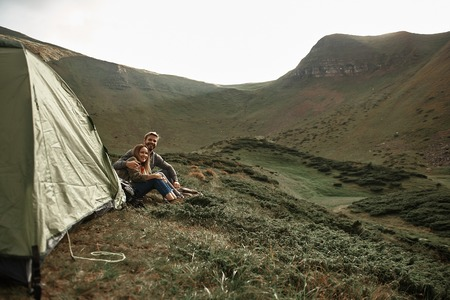 Happy hikers. Positive young couple of hikers smiling and cuddling while relaxing near their tent Stock Photo