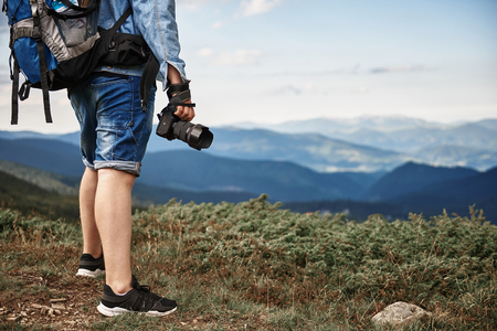 Professional experienced photographer holding his modern camera while traveling in the mountains Stock Photo