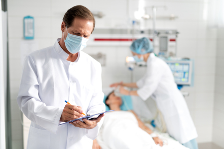 Waist up portrait of male doctor in protective mask writing down information about condition of young lady on clipboard. Female assistant doing artificial inhalation on blurred background