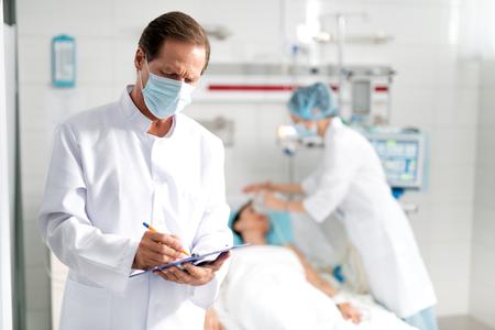 Taille hoch Porträt des männlichen Arztes in der Schutzmaske, die Informationen über den Zustand der jungen Dame auf Zwischenablage aufschreibt. Weibliche Assistentin, die künstliches Einatmen auf unscharfem Hintergrund tut Standard-Bild