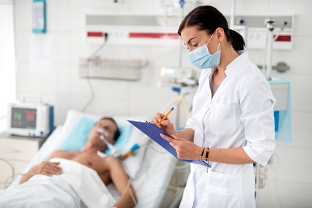 Side view portrait of young lady in protective face mask holding clipboard and noting information about condition of middle aged man. Gentleman on breathing machine lying in hospital bed on blurred background Reklamní fotografie
