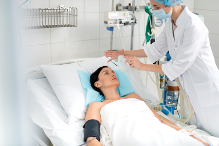 I am feeling unwell. Young lady lying in hospital bed while female anesthesiologist in protective mask doing artificial inhalation Stock Photo