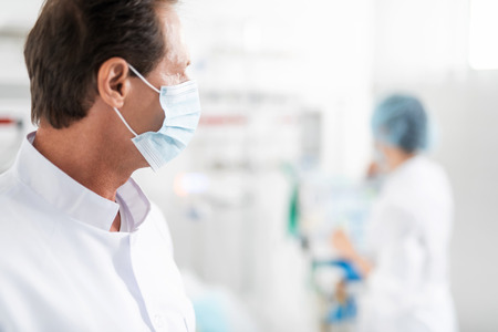 Close up side view portrait of handsome middle aged man in sterile medical uniform looking at nurse. Copy space in right side