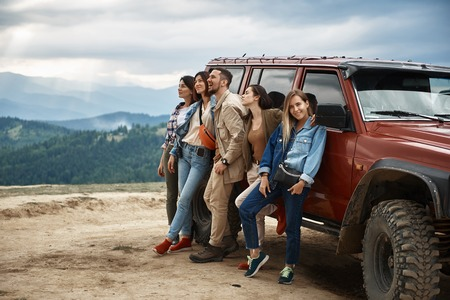 Group of positive young people leaning on the off road car while resting in the mountains Stock Photo