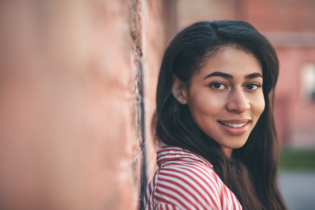 Dark haired woman. Pretty long haired young woman standing against the brick wall and smiling friendly while looking at you Stock Photo