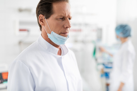 Close up portrait of handsome middle aged man in white lab coat looking away with serious thoughtful expression. Nurse on blurred background