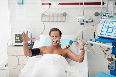 Portrait of enraged patient on mechanical ventilator lying in bed and looking at camera with grimace on his face. He is raising hands and screaming with madness