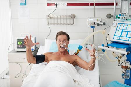 Portret van woedende patiënt op mechanische ventilator die in bed ligt en camera met grimas op zijn gezicht bekijkt. Hij steekt zijn handen op en schreeuwt van waanzin