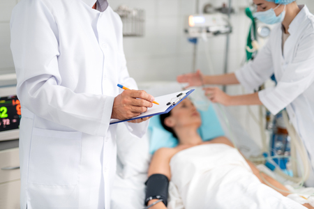 Cropped portrait of male therapist in white lab coat writing down information about condition of young lady on clipboard. Female assistant doing artificial inhalation on blurred background Stock Photo