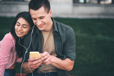Listening to music. Happy long haired woman smiling and closing her eyes while listening to music in earphones together with her cheerful boyfriend