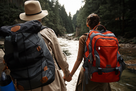 Enthusiastic young couple of hikers carrying heavy backpacks and holding hands while looking at the mountain river