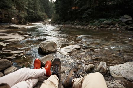 Active people wearing comfortable shoes and relaxing on the stone near the mountain river while traveling 写真素材