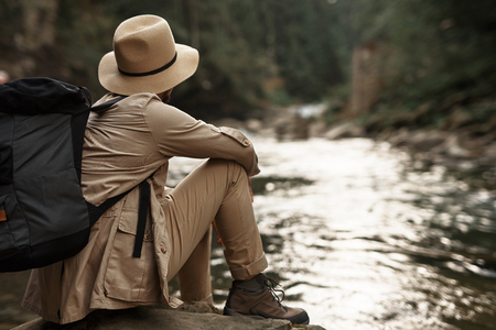 Young man carrying backpack and wearing his hat while sitting near the river during the journey