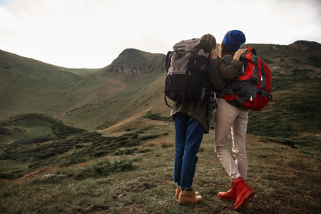 Active young hikers standing close to each other and wearing backpacks while traveling in the mountains Stock Photo