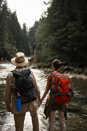 Calm active couple holding hands and looking into the distance while standing with big backpacks and looking at the beautiful river