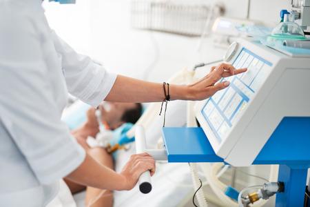 Cerca de manos femeninas comprobando equipos médicos. Paciente en respirador acostado en la cama sobre fondo borroso