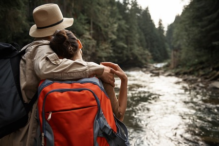 Peaceful young couple of active travelers standing with big backpacks and hugging while admiring the beauty of nature