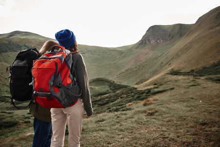 Two young women carrying big heavy backpacks and wearing comfortable clothes while traveling and looking at the landscape