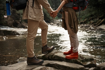 Close up of beautiful active couple of hikers standing in front of each other and holding hands