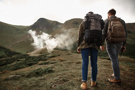 Morning in mountains. Couple of hikers enjoying spending time in the mountains and holding hands while walking