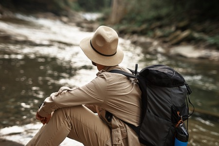 Tired hiker carrying big backpack and looking at the water stream while relaxing near it