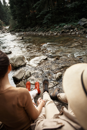 Romantic young couple holding hands and looking at the beautiful mountain river while sitting on the big stone 写真素材