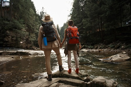 Young couple of active travelers holding hands and looking at the water stream while standing on the stone