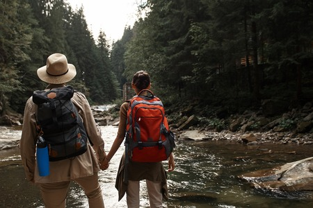 Active young hikers holding hands and carrying heavy backpacks while looking at the beautiful river