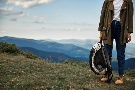 Backpack in hand. Young experienced traveler wearing comfortable clothes while being in the mountains with big backpack
