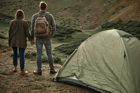 Young romantic couple holding hands while standing near the mountain and admiring the view of the mountains