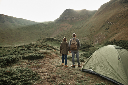 Peaceful relaxed young man and woman standing near the tent and holding hands while looking at the landscape