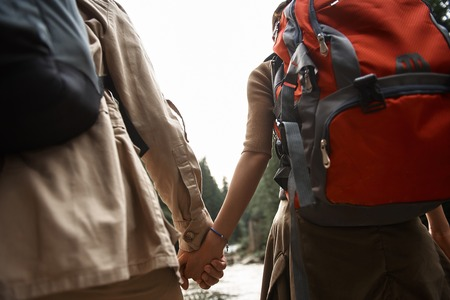 Close view of two travelers carrying heavy backpacks and holding hands while traveling