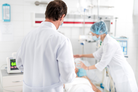 Back view of therapist in white lab coat monitoring condition of sick lady. Female assistant in sterile uniform doing artificial inhalation on blurred background