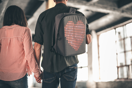 Heart on backpack. Young man wearing casual clothes and carrying backpack while holding hands with his dark haired girlfriend