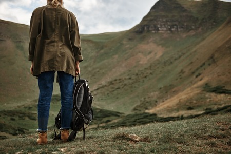 Woman with backpack. Young woman standing with her back to the camera and looking at the hills while carrying her backpack