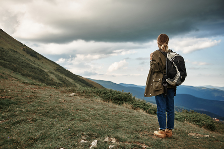 Calm young woman carrying her big heavy backpack and peacefully looking at the beautiful landscape Stock Photo