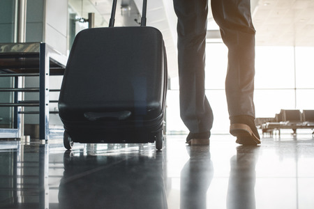 Businessman carrying suitcase on wheels and moving forward. Focus on baggage