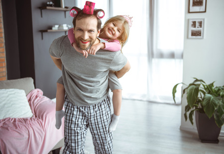 Happy family. Portrait of excited girl sitting on daddy back and laughing. Man is standing at home and looking at camera with cheerfulness. He wear makeup and rollers on hair